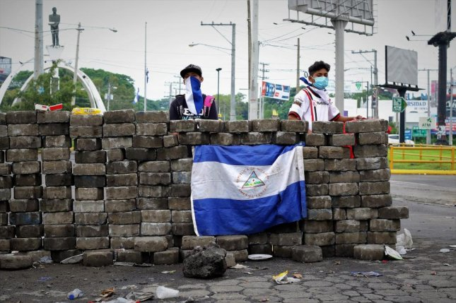 Two anti-government protesters, ages 15 and 16, guard a roadblock on a major intersection in Managua on Sunday. Many of the protesters guarding roadblocks are in their teens and early 20s. Photo by Ray Downs/UPI