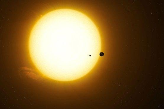 An illustration shows a moon orbiting around a planet as the pair cross the face of their host star