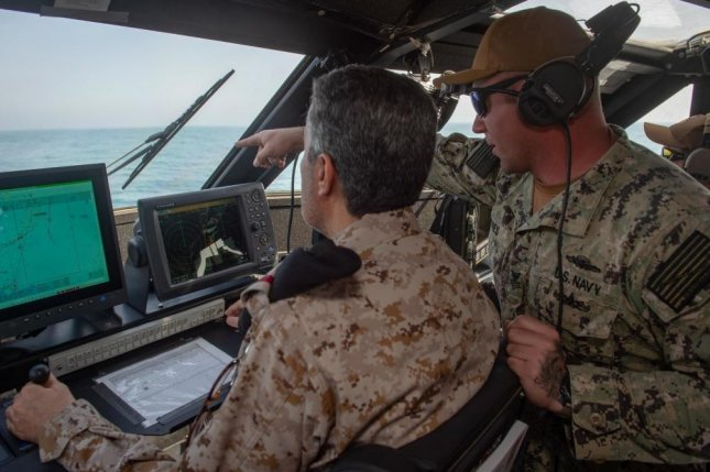 Gunner's Mate 1st Class Andrew Davies, assigned to Commander Task Force 56, guides Rear Adm. Majed Haz'z Al-Kahtani, Deputy Commander, Royal Saudi Naval Forces Eastern Fleet, on how to operate a Mark VI patrol boat during an underway as part of exercise Nautical Defender 20 in Jubail, Kingdom of Saudi Arabia Feb. 23. Photo by Kory Alsbery/U.S. Navy
