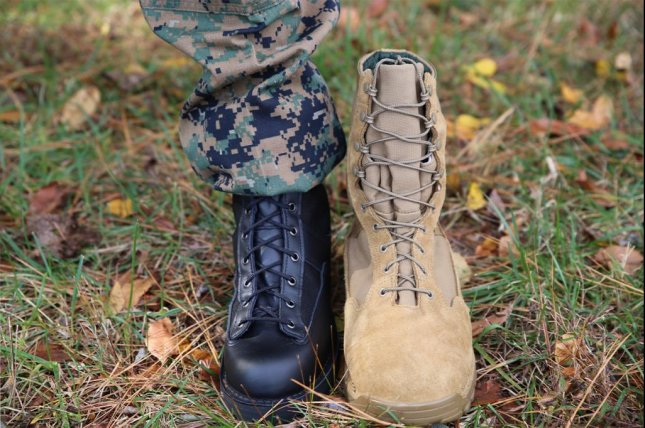 Capt. Caleb Haney, a project officer with the Program Manager for Infantry Combat Equipment at Marine Corps Systems Command, compares the updated Marine Corps Intense Cold Weather Boot with an earlier, bulkier, suede prototype November 13 aboard Marine Corps Base Quantico, Va. Photo by Matt Gonzales/U.S. Marine Corps