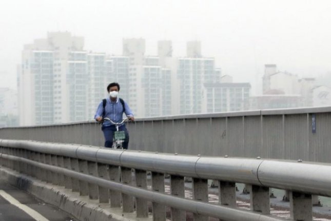 A man wearing a mask crosses a bridge on a bike in heavy air pollution in Seoul on May 14, 2018. Photo by Yonhap