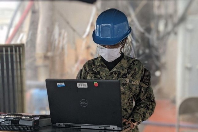 A sailor aboard the dock landing ship USS Tortuga uses a laptop computer with software designed to track the possible spread of the COVID-19 virus aboard the ship. Photo courtesy of U.S. Navy