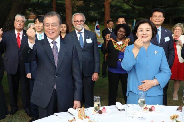 South Korean President Moon Jae-in, first lady Kim Jung-sook (R) and Seoul-based diplomats make finger heart gestures at the presidential Blue House on Friday. Photo by Yonhap/EPA-EFE