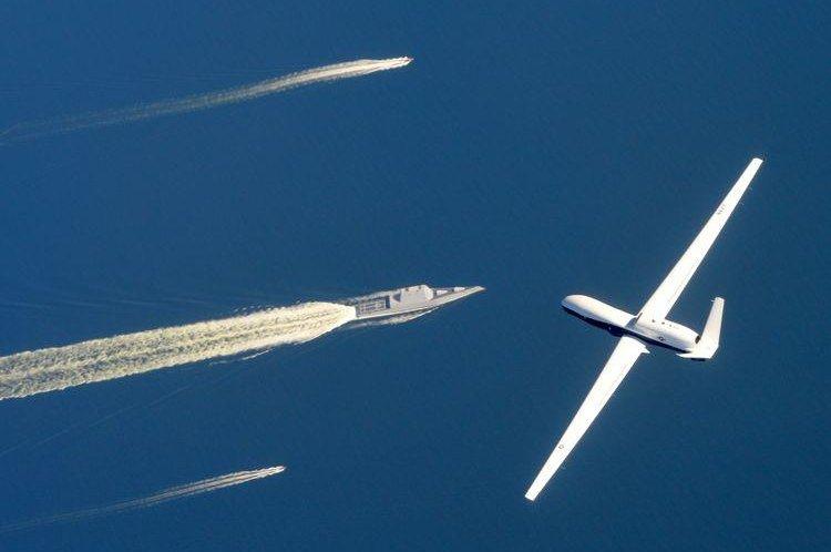 A U.S. Navy MQ-4C Triton flies over the USS Zumwalt. Photo courtesy of Northrop Grumman