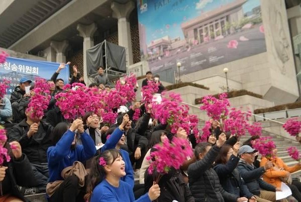 Pro-North Korea activists wave pink flowers at an event in Seoul to announce their support for North Korean leader Kim Jong Un's unscheduled visit to Seoul. South Korean President Moon Jae-in invited Kim to Seoul during the summit in September in the North Korean capital of Pyongyang. Photo by National Sovereignty Association