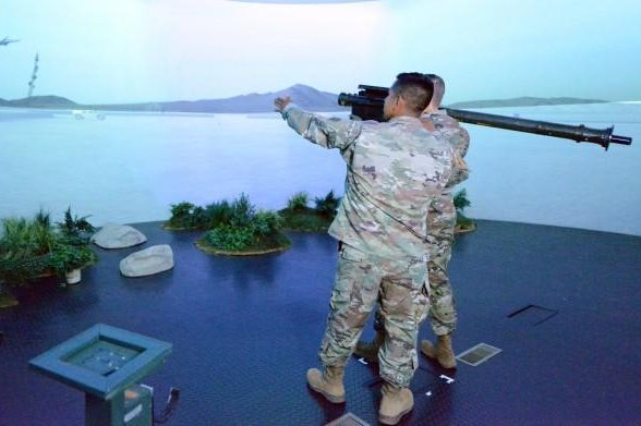 In the Stinger Dome, Staff Sgt. Ivan Peralta guides Sgt. 1st Class Arianna Cook as she aims a shoulder-fired Stinger missile at an enemy helicopter projected on the circular wall of the simulation center. Photo via U.S. Army