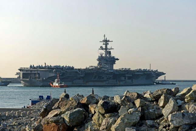 The aircraft carrier USS Carl Vinson approaches the Republic of Korea Fleet headquarters in the port of Busan. The carrier left Singapore on Saturday and was headed to Australia but instead ordered to return to the Korean Peninsula. Photo by Jermaine M. Ralliford/U.S. Navy