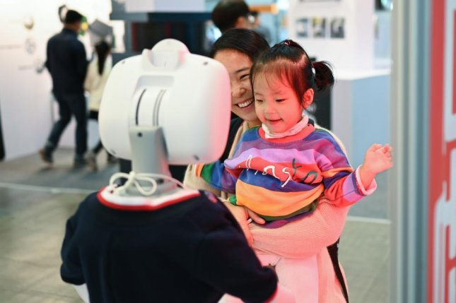 A mother and daughter interact with a friendly robot at the Robotworld 2019 trade show in Seoul on Saturday. Photo by Thomas Maresca/UPI