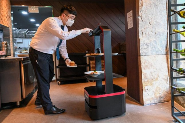 A server places food on Aglio Kim, an AI-powered server robot being used at a restaurant in Seoul. Photo by Thomas Maresca/UPI