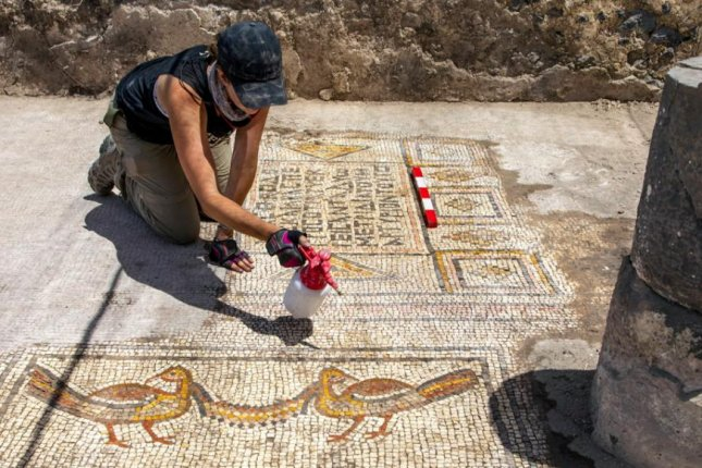 Jessica Rentz cleans a pair of birds holding a garland, foreground, and one of the dedication inscriptions in the mosaic, rear, of the Burnt Church in July. Photo by Michael Eisenberg