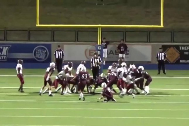 A football strikes the referee's head before bouncing up for a successful extra point. Marshall Hughes/YouTube video screenshot