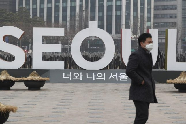 A South Korean man wearing a facial mask walks in front of Seoul city hall on Tuesday. Photo by Jeon Heon-Kyun/EPA-EFE