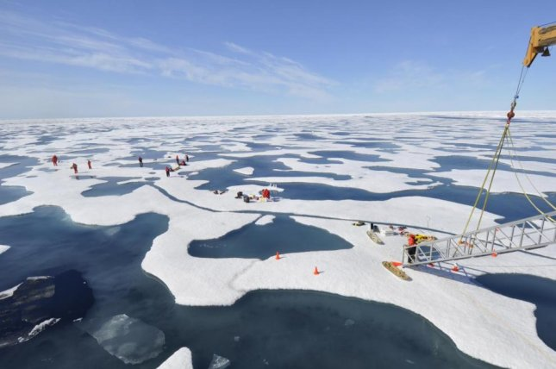 Researchers are seen studying melt ponds in the Arctic. Photo by Gert van Dijken