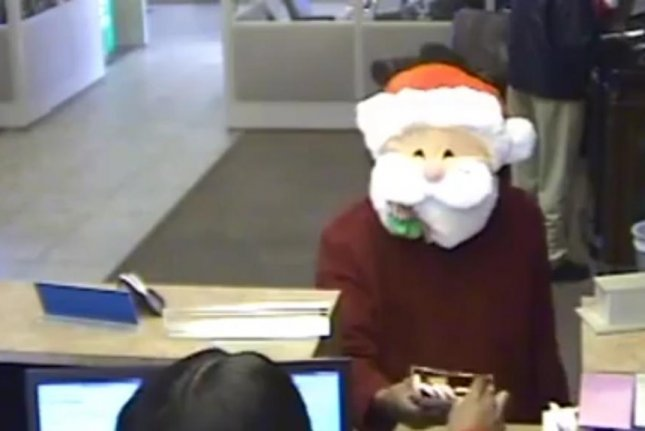 Santa Claus hands out candy canes at a Memphis, Tenn., bank moments before robbing one of the tellers. Screenshot: Memphis Police Department/Facebook