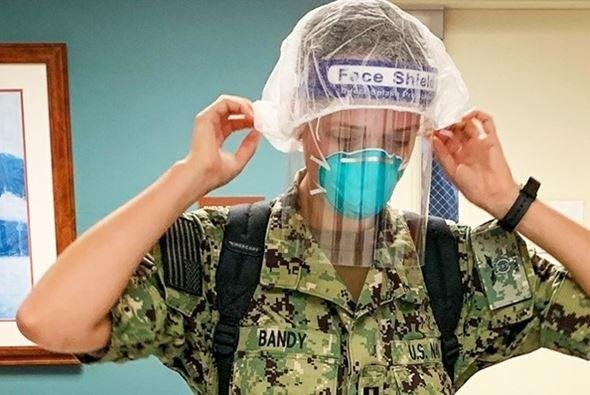 Lt. Tess Bandy of the Naval Medical Center, Camp Lejeune, N.C., dons personal protective equipment in preparation for training. The Defense Department announced increases in personal medical protective equipment as COVID-19 cases in the military rise. Photo by Maj. Bonnie Conard/U.S. Army