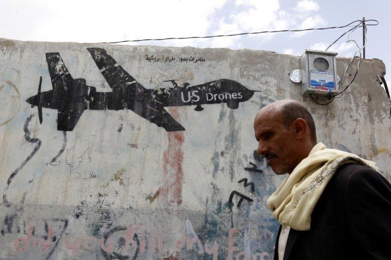 A Yemeni man walks past graffiti depicting a U.S. drone in Sanaa, Yemen, on August 22. Photo by Yahya Arhab/EPA-EFE