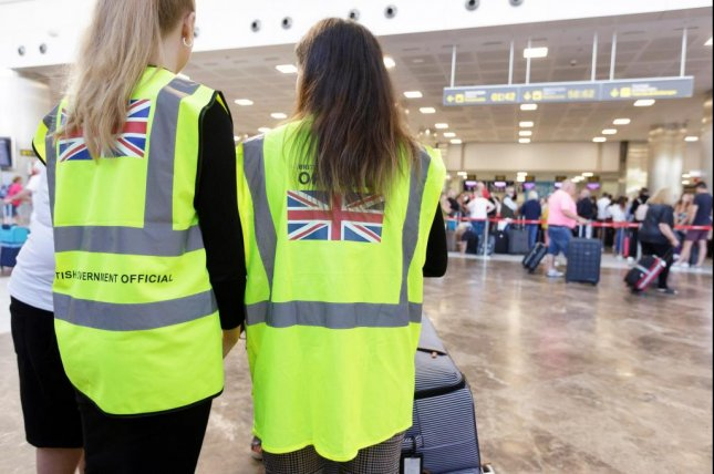 Two British Government's officials speak with a traveler at Tenerife Sur airport, in Tenerife Island, Spain, Tuesday. British regulators said Tuesday they are considering an investigation into the collapse of travel firm Thomas Cook. Photo by Ramo de la Rocha.EPA-EFE