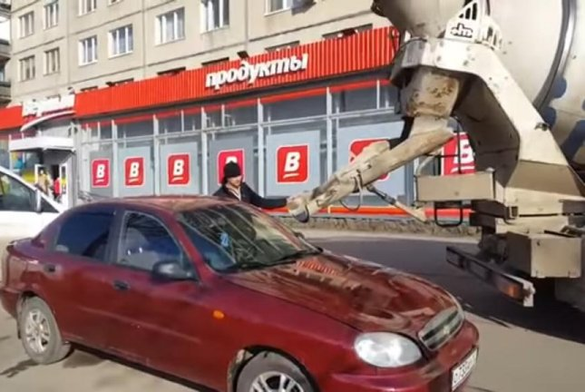 A Russian man uses a cement-mixing truck to fill his wife's car with wet cement. Screenshot: AhtubaTV/YouTube