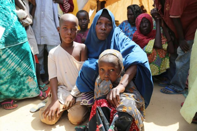 A displaced woman with her two sons in a camp in Maiduguri, Nigeria. Human Rights Watch said women in camps are routinely sexually victimized by officials. Photo courtesy of U.N. Office for the Coordination of Humanitarian Affairs/ Jaspreet Kindra.     Rukkaya with her two surviving children in Dalori camp in Maiduguri. Her 17-year-old son was killed and a 15-year-old kidnapped by Boko Haram. Credit: OCHA/Jaspreet Kindra.
