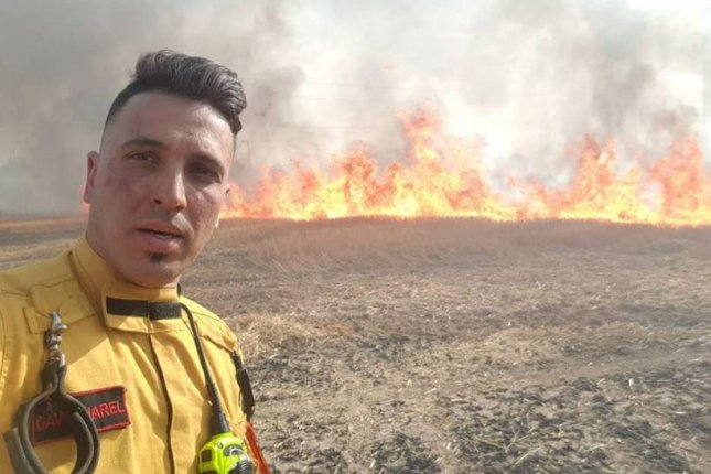 An Isreli firefighter takes a break while battling flames near the Gaza border. High temperatures from an enduring heat wave sparked brush fires along the border and blazes in three of Israel's largest forests. Photo courtesy Friends of Israel Fire Fighters/Facebook