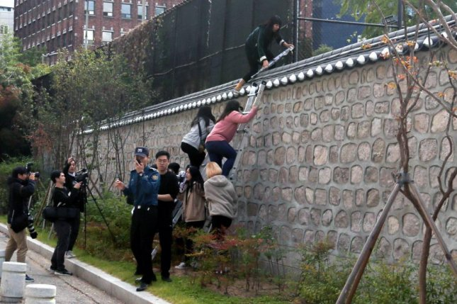 South Korean university students climb over a wall during a protest against the Special Measures Agreement, at Habib House, the U.S. ambassador's residence, in Seoul on Friday. Photo by Kim Chul-soo/EPA-EFE