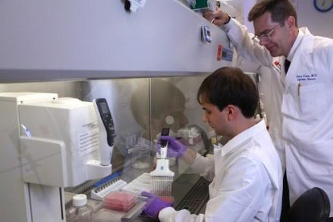 """Dr. James Crowe, director of the Vanderbilt Vaccine Center, watches graduate student Andrew Flyak """"plate"""" antibody-producing B cells from people in Africa who have survived infection by the Ebola virus. Photo by Anne Rayner/Vanderbilt University"""