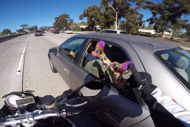 A motorcyclist on a stretch of California highway reaches out to touch a foot hanging out from a car window. Zim Killgore/YouTube video screenshot