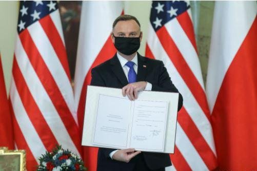 Polish President Andrzej Duda displays the enhanced defense agreement between the United States and Poland, which signed on Monday in Warsaw. Photo courtesy of Office of the Polish President
