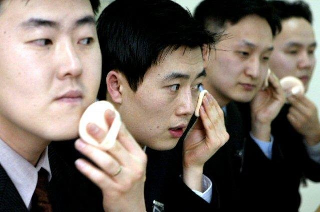 South Korean men applying makeup during a cosmetics firm training session. Cosmetics companies have tackled their target groups with savvy marketing. Photo by Yonhap.