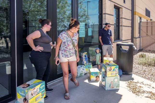 From left to right, Meagan O'Toole-Pitts, Ashley Cortez, Oliver Cortez and his father, Mark Cortez, attempt to drop off diapers and toys for detained children at the immigration detention center in Clint, Texas. Photo courtesy of Armando Martinez Photography