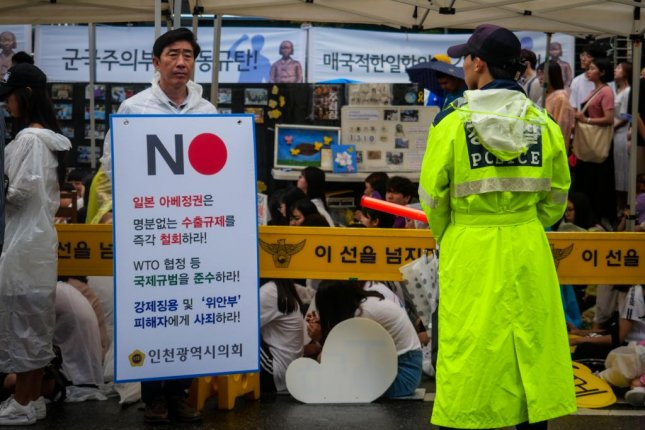 A protester in front of the Japanese Embassy in Seoul holds a sign calling for a boycott of Japanese products. Photo by Thomas Maresca/UPI