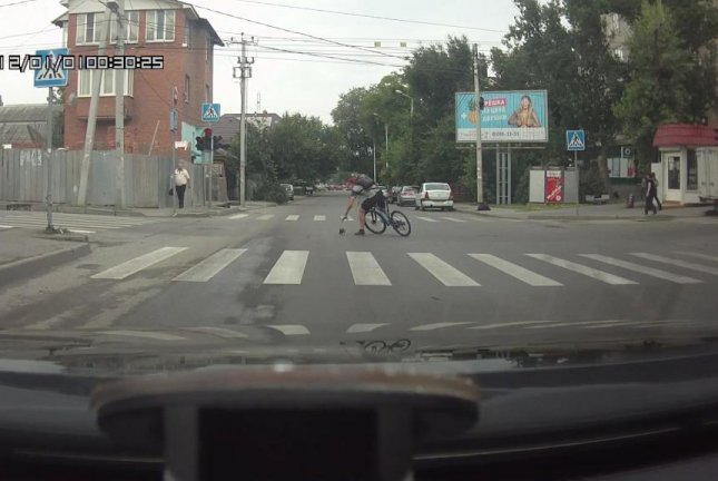 A cyclist stops in a Rostov intersection to rescue a wandering kitten. Screenshot: JukinMedia