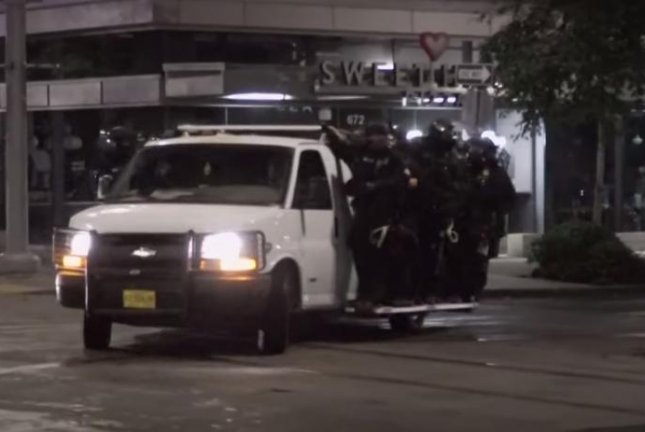 Riot police travel toward a demonstration in Portland, Ore., Friday. Image via KGW News/YouTube