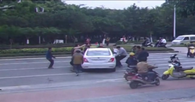 Witnesses lift a car to free a trapped cyclist in China. Newsflare video screenshot