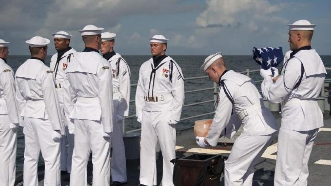 U.S. Navy personnel carry the cremated remains of Apollo 11 astronaut Neil Armstrong during a burial-at-sea service aboard the USS Philippine Sea in the Atlantic Ocean. Armstrong, the first man to walk on the moon during the 1969 Apollo 11 mission, died Aug. 25. Credit: (NASA/Bill Ingalls)