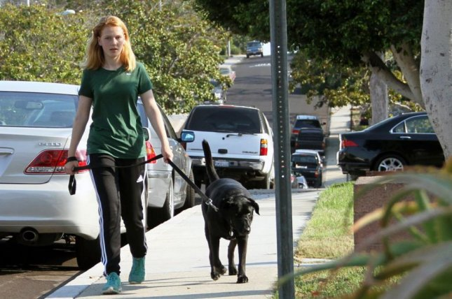 Kennedy Dierk, 14, walks her dog while recovering from a concussion. Many parents restrict their kids' activity too long during the recovery process, potentially prolonging recovery or making their condition worse, doctors say. Photo by Barb Consiglio/University of California Los Angeles