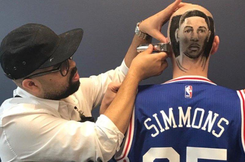 Barber Kenny Duncan shaves Ben Simmons' face onto the head of Philadelphia 76ers senior vice president of sales and service Jake Reynolds. (JakeReynolds24/Twitter)