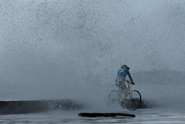 A man cycles along a dike in Legazpi, Philippines, Tuesday after Typhoon Kammuri made landfall, forcing many evacuate. Photo by Zalrian Sayat/EPA-EFE
