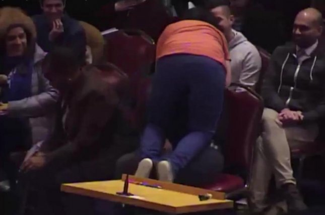 Dancer Sara Juli climbs on a man and pretends to vomit during her dance performance at a Portland City Council meeting in Maine. Screenshot: WGME-TV