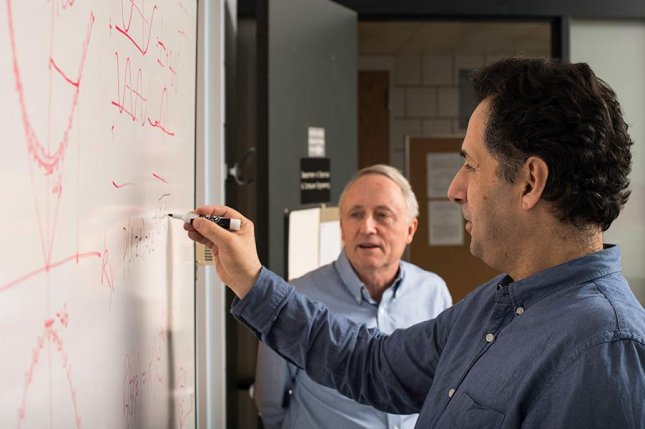 Engineering professor Kevin Parker looks on as Miguel Alonso, professor of optics, works out the analytically beautiful mathematical solution that inspired a new precise and powerful beam pattern. Photo by J. Adam Fenster/University of Rochester