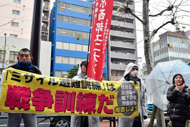 Protesters shout slogans against a missile evacuation drill organized at an amusement park near Tokyo Dome stadium in Tokyo on Monday. The red characters on the banner read, It's a war exercise! Photo by Franck Robichon/EPA-EFE
