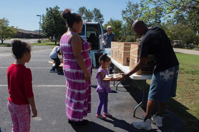 Members from Zion Hill Baptist Church give out home-cooked meals in the parking lot of St. Paul's High School, an American Red Cross-run shelter, on Thursday. Photo by Patty Vassar Nieberg/Medill News Service