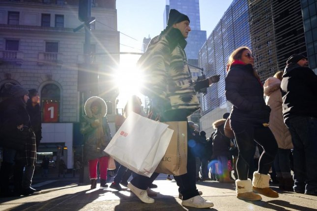 People carry shopping bags during the Christmas season in New York on Friday. United Parcel Service is predicting record returns on Jan. 2. Photo by Justin Lane/EPA-EFE