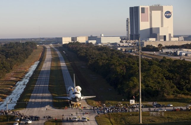 Space shuttle Atlantis moves down the Kennedy Parkway on its 76-wheeled orbiter transporter system. In the background is the Vehicle Assembly Building. Credit: NASA/Kim Shiflett