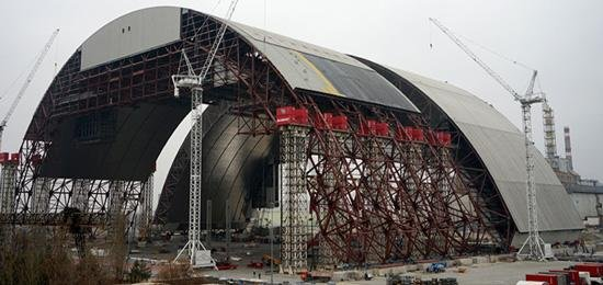 A steel containment shell, 540 feet high, will cover the ruined Chernobyl nuclear reactor. The shell, expected to be put in place in 2017, will replace a solid concrete sarcophagus poured over the reactor in the months after the disaster. The original containment was meant to last three decades. Photo courtesy of World Nuclear Association/European Bank for Reconstruction and Development