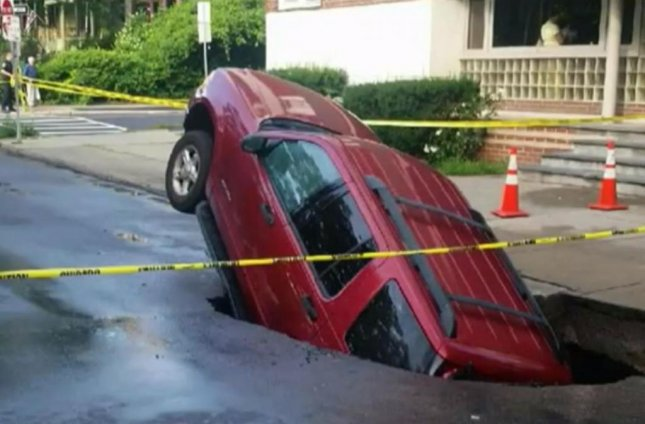 A large sinkhole swallowed an SUV in Albany on Tuesday. Officials said that a large water main broke in the area and cleared the ground underneath the street, creating the hole.  Screen capture/WNYT/Inform Inc.