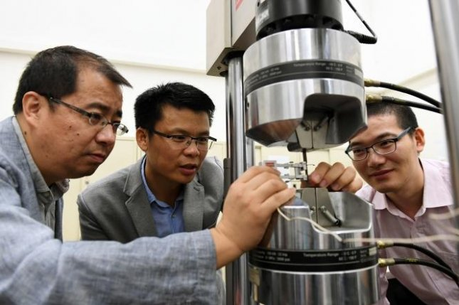 The research team uses a tensile machine to test the yield strength and elongation of steel. Pictured from right are He Binbin, Huang Mingxin and Luo Haiwen, whose engineering teams developed the new super steel. Photo courtesy of the University of Hong Kong