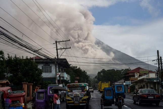 Residents evacuate the town of Carmalig in the Philippines' Albay province on Monday, as the alert level from the eruption of Mount Mayon was raised to Level 4. Photo by Linus Esconder II/EPA-EFE