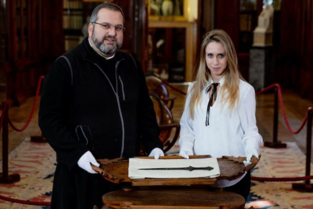 Father Serafino Jamourlian of the San Lazzaro degli Armeni Museum, and doctoral candidate Vittoria Dell'Armellina, of the Ca' Foscari University of Venice, display a sword housed in the museum and found to be a 5,000-year-old relic of the Bronze Age. Photo by Andrea Avezzi/Ca' Foscari University of Venice