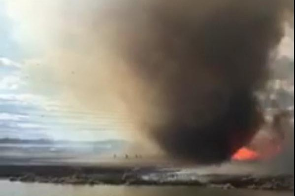 A grass fire started by an out-of-control campfire in St. Albert, Alberta, becomes a fire tornado. Screenshot: Storyful